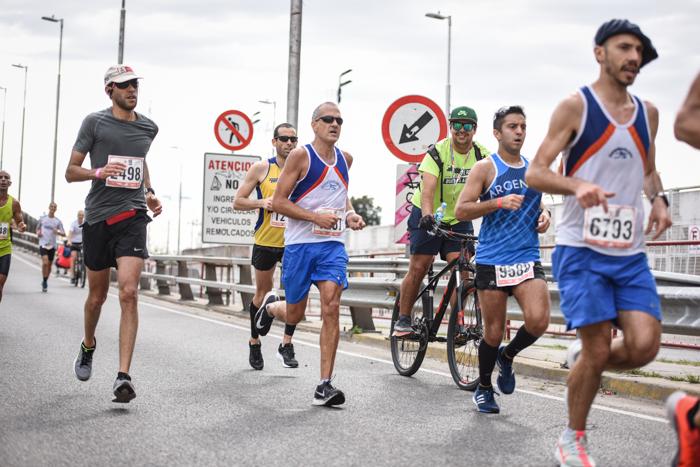 Gente con bicicleta en plena maratón